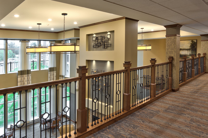 View Looking Down on Two-Story Town Center Lobby With Large Windows Over Wooden Railing
